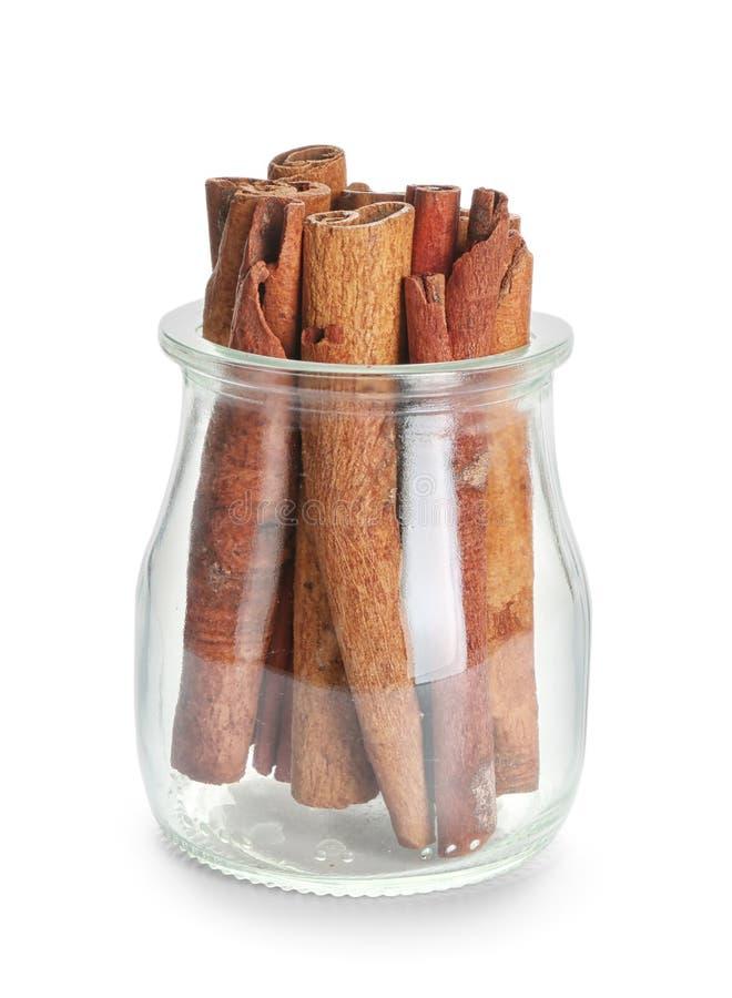 Frasco de vidro com as varas de canela no fundo branco fotografia de stock