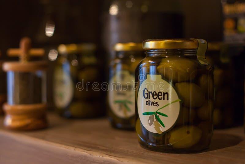Frasco de vidro com azeitonas verdes imagem de stock royalty free
