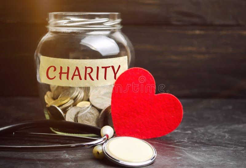 Frasco de vidro com a caridade das palavras e o coração O conceito de acumular o dinheiro para doações saving Ajuda médica social imagens de stock