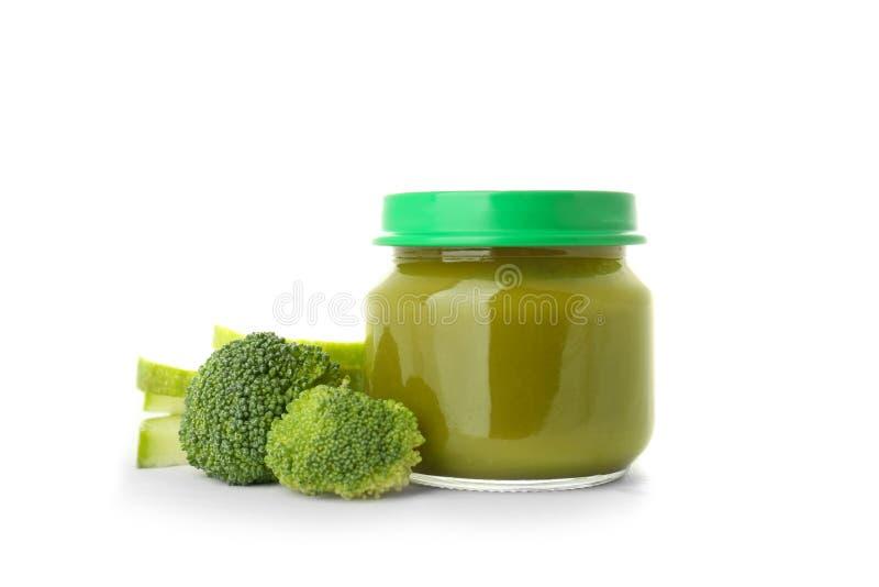 Frasco de vidro com comida para bebê e brócolis saudáveis no fundo branco fotografia de stock