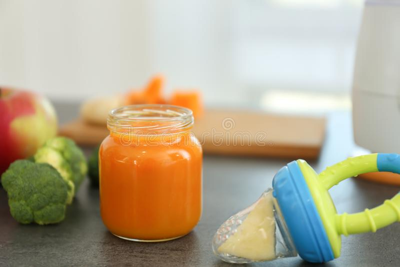 Frasco de vidro com comida para bebê recentemente preparado na mesa de cozinha fotos de stock royalty free