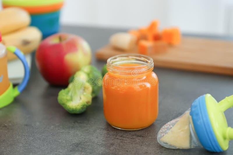 Frasco de vidro com comida para bebê recentemente preparado na mesa de cozinha imagens de stock