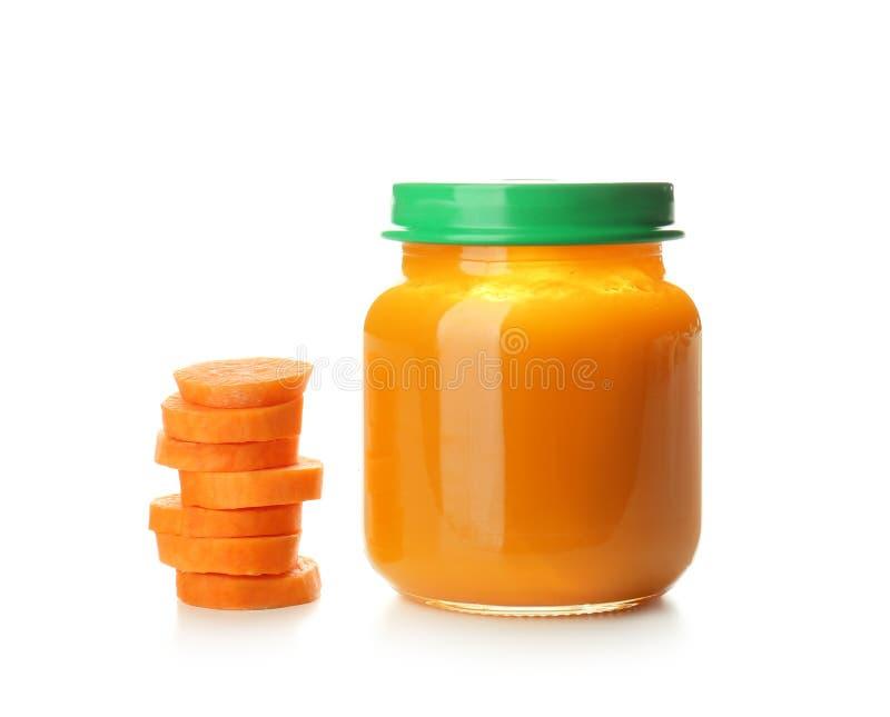 Frasco de vidro com comida para bebê saudável e a cenoura cortada no fundo branco foto de stock royalty free