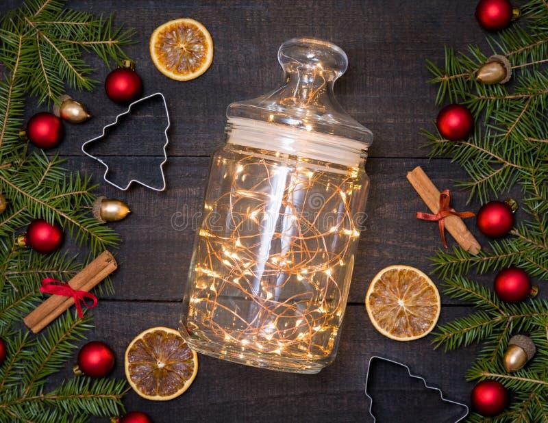 Frasco de vidro com luzes de Natal no fundo rústico de madeira escuro fotografia de stock royalty free