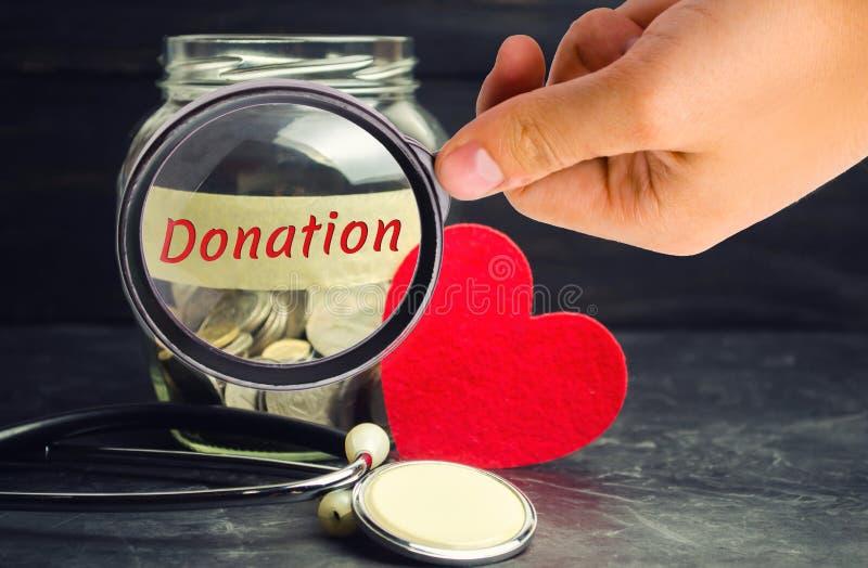 Frasco de vidro com moedas, coração e estetoscópio e a inscrição 'doação ' Conceito da medicina transfusão de sangue, cuidados mé fotografia de stock royalty free
