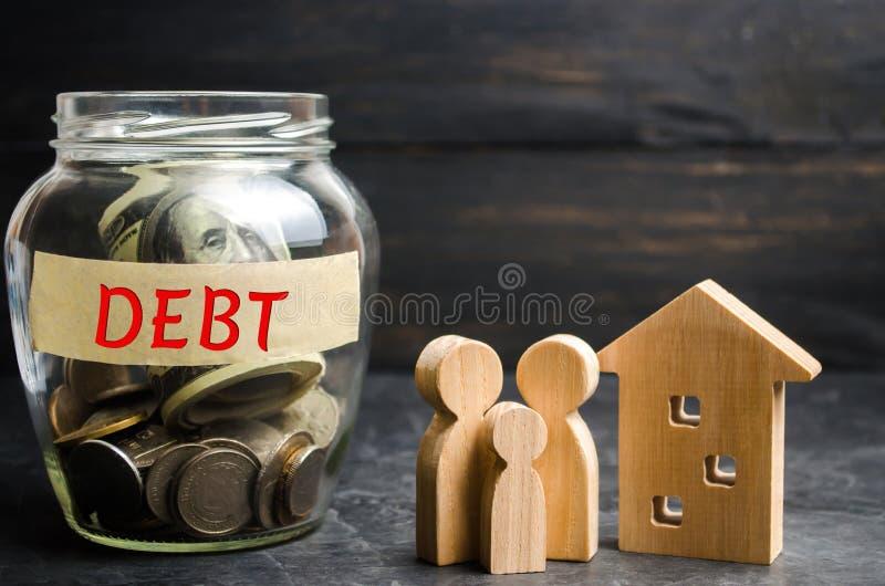 Frasco de vidro com moedas e a inscrição 'débito ', família e casa de madeira Bens imobiliários, economias de casa, conceito do m fotos de stock