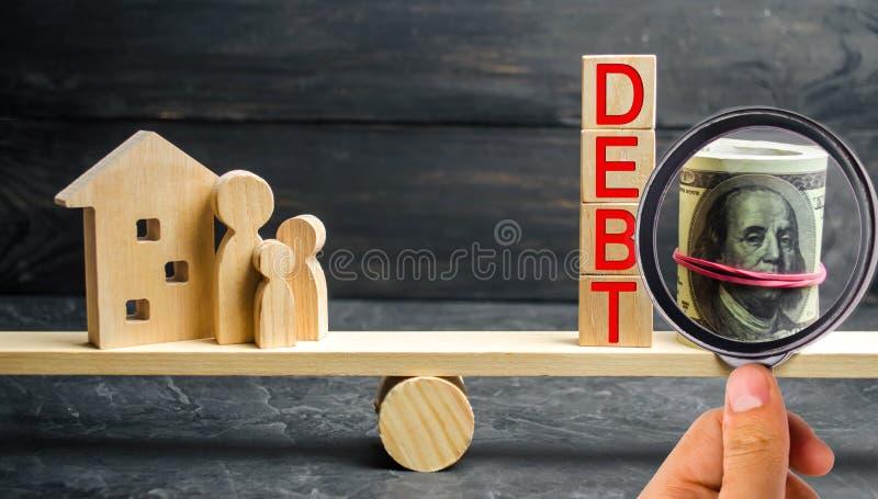 Frasco de vidro com moedas e a inscrição 'débito ', família e casa de madeira Bens imobiliários, economias de casa, conceito do m imagens de stock royalty free