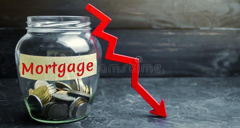 Frasco de vidro com moedas e a inscrição 'hipoteca 'e para baixo seta Interesse reduzido na hipoteca Baixas taxas de juro queda fotos de stock