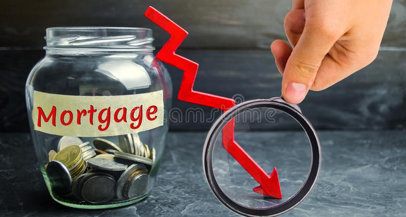 Frasco de vidro com moedas e a inscrição 'hipoteca 'e para baixo seta Interesse reduzido na hipoteca Baixas taxas de juro queda fotografia de stock