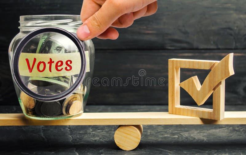 Frasco de vidro com moedas e os votos das palavras 'e uma caixa de seleção nas escalas Conceito da votação para o dinheiro Suborn foto de stock