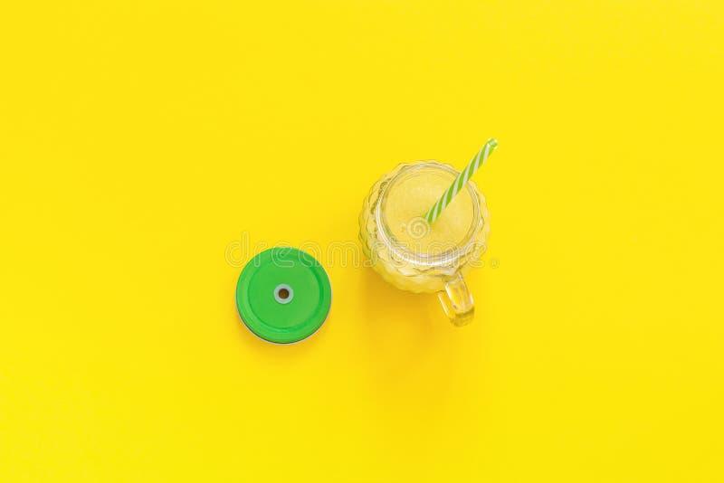 Frasco de vidro com suco, o batido ou o fresco amarelo natural de fruto com tampa e palha verdes do cocktail no fundo amarelo alt fotografia de stock