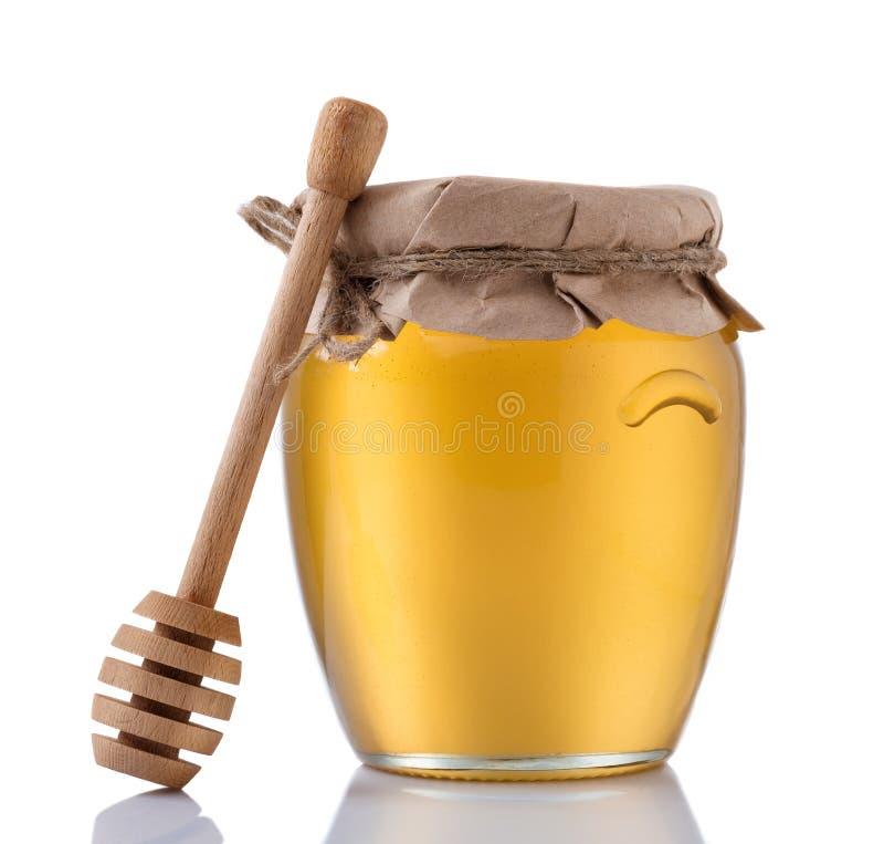 Frasco de vidro completamente do mel e da vara de madeira em um fundo branco imagem de stock