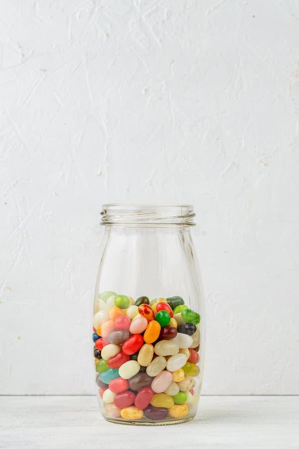 Frasco de vidro completamente de feijões de geleia coloridos fotografia de stock