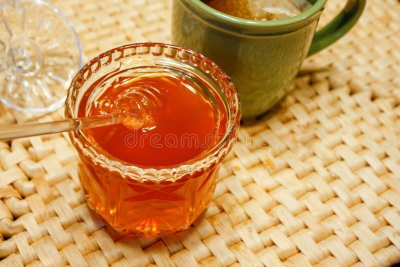Frasco de vidro completo do mel na esteira de lugar tecida colorida natural fotografia de stock