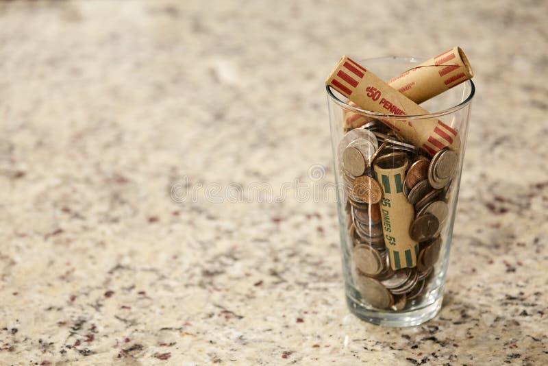 Frasco de vidro das moedas no copo no dinheiro pobre rico do mercado da mudança da riqueza da finança do dólar do banco do débito fotografia de stock