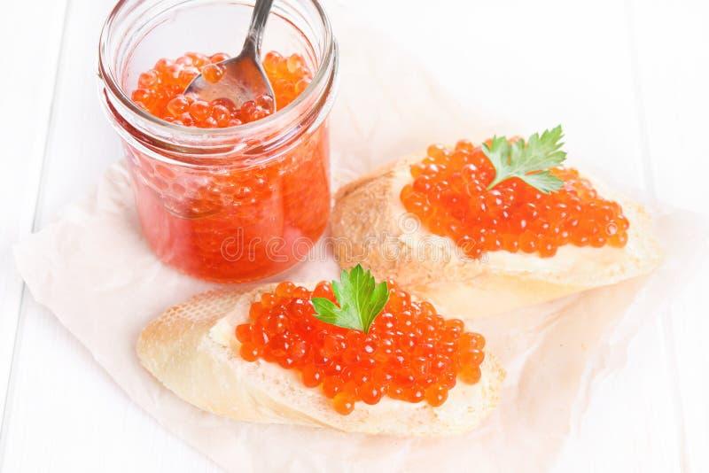 Frasco de vidro do caviar e de petiscos vermelhos no fundo branco imagem de stock royalty free