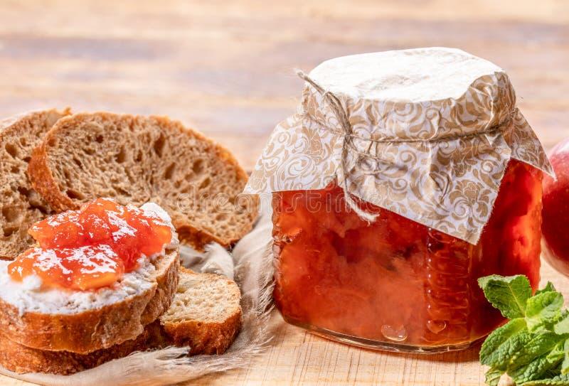 Frasco de vidro do close-up completamente do doce da maçã, pão cortado, manchado com o doce do coalho e da maçã no fundo de madei fotos de stock royalty free