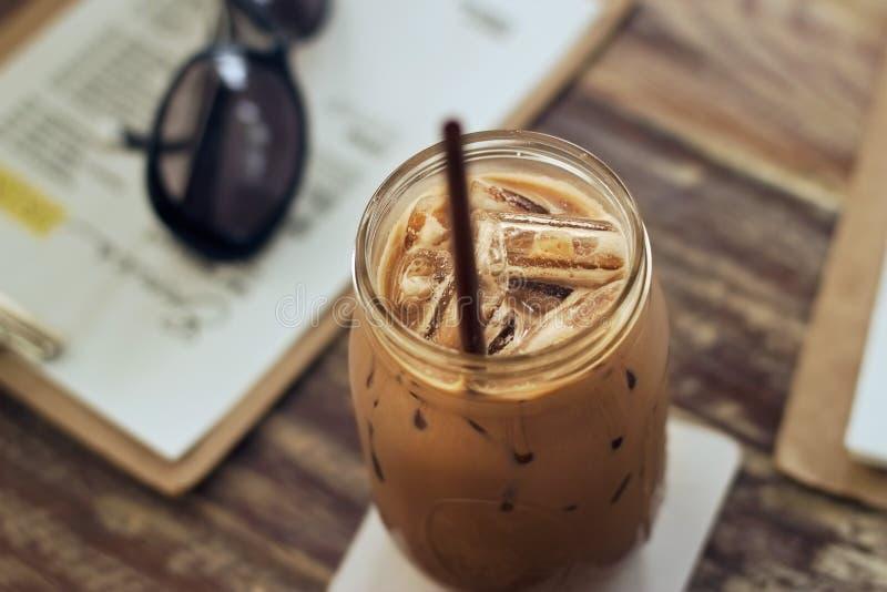 Frasco de vidro do leite de chocolate com gelo na tabela na cafetaria fotografia de stock