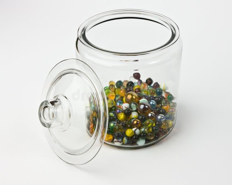 Frasco de vidro meio cheio de mármores de vidro coloridos fotos de stock royalty free