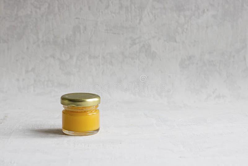 Frasco de vidro pequeno com o tampão do metal com claro - isolado amarelo do mel no fundo cinzento do cimento com espaço da cópia fotografia de stock royalty free