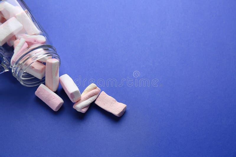Frasco de vidro virado com o marshmallow saboroso no fundo da cor fotos de stock