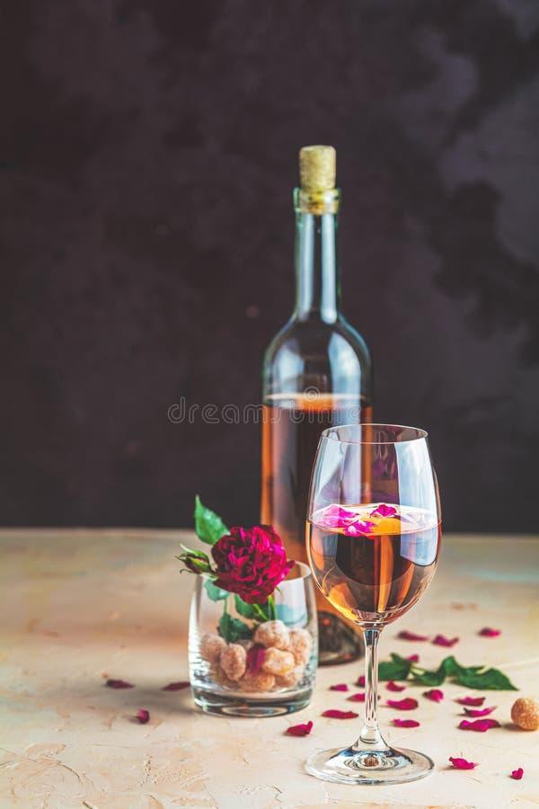 Frasco de vinho de rosa e de vidro servido com vinho de rosa e pétalas de rosa, rosa e fruta cristalizada em vidro sobre uma mesa fotografia de stock