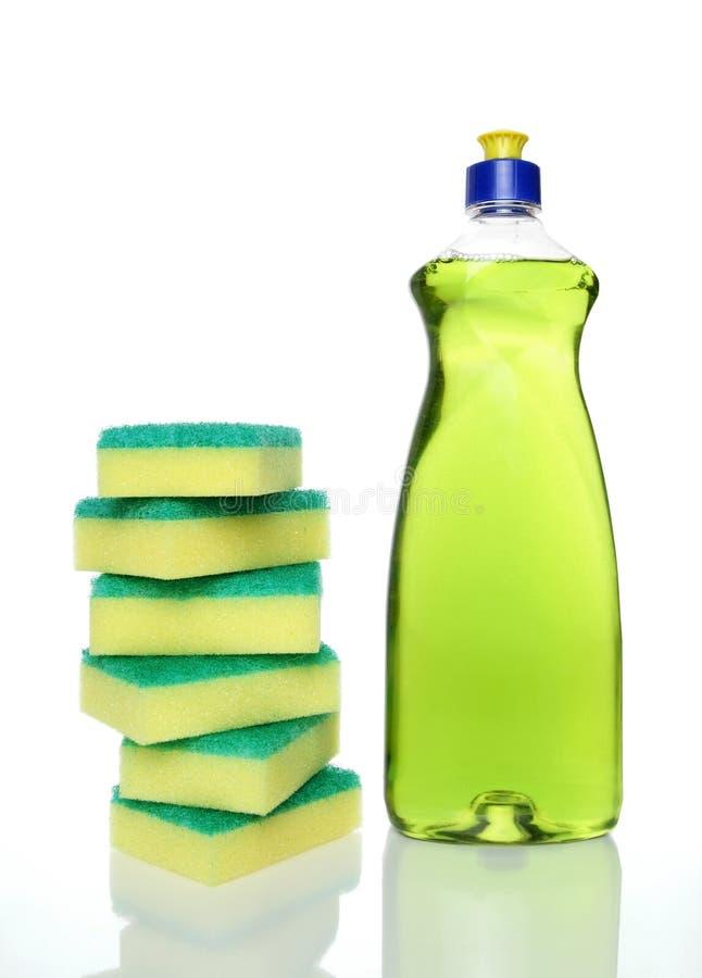Frasco do líquido e de esponjas verdes da lavagem da louça fotos de stock royalty free