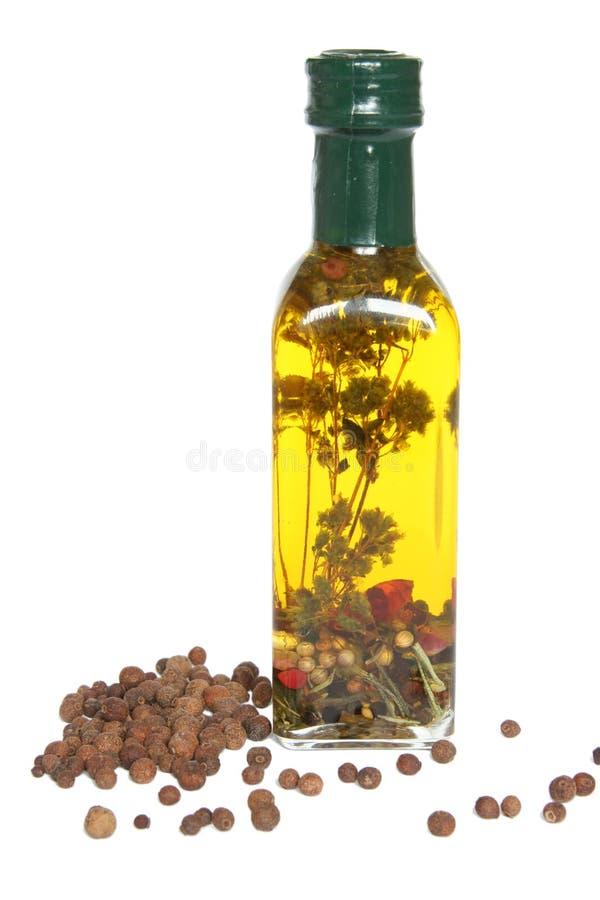Frasco do petróleo verde-oliva com especiarias e ervas imagem de stock