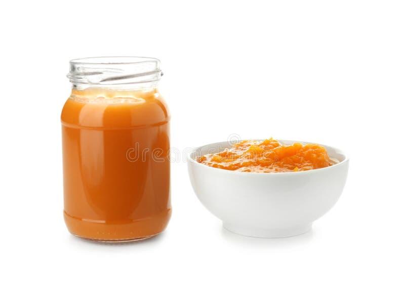 Frasco e bacia de vidro com comida para bebê saudável no fundo branco imagem de stock