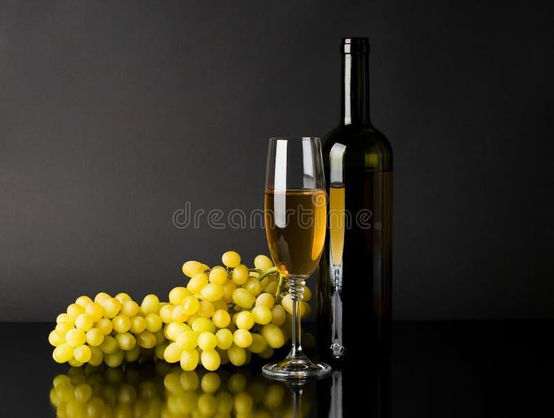 Frasco e vidro do vinho branco com uvas imagem de stock