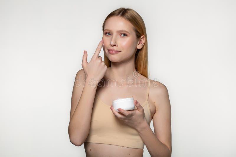 Frasco louro bonito da proposta da mulher do creme do creme hidratante Cara fresca da jovem mulher do close-up Isolado no branco imagens de stock