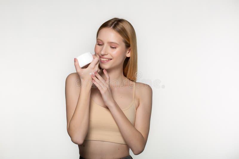 Frasco louro bonito da proposta da mulher do creme do creme hidratante Cara fresca da jovem mulher do close-up Isolado no branco foto de stock