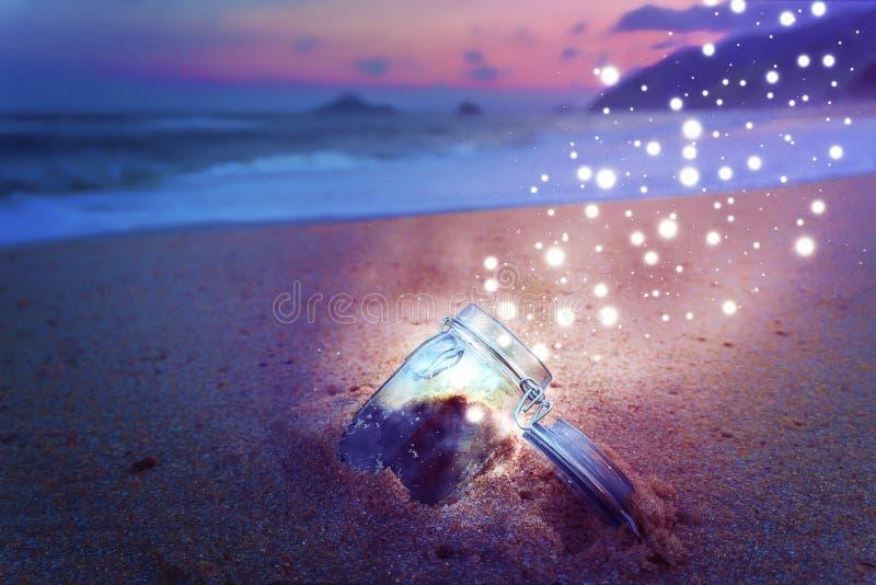 Frasco mágico aberto na praia na noite que libera o conceito criativo da poeira de estrela foto de stock