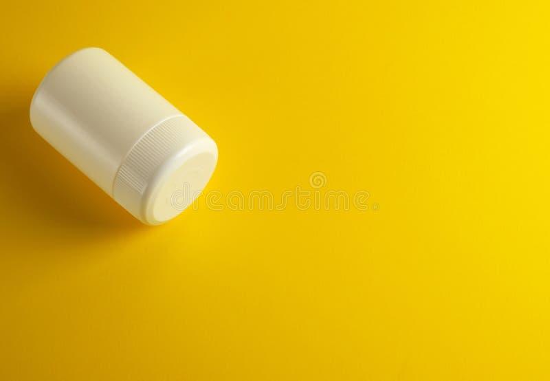 frasco plástico branco fechado para medicinas em um fundo amarelo fotos de stock royalty free