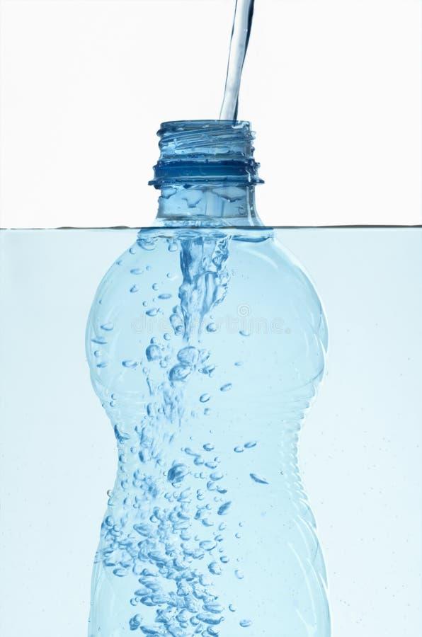 Frasco plástico na água com bolhas para dentro fotografia de stock royalty free