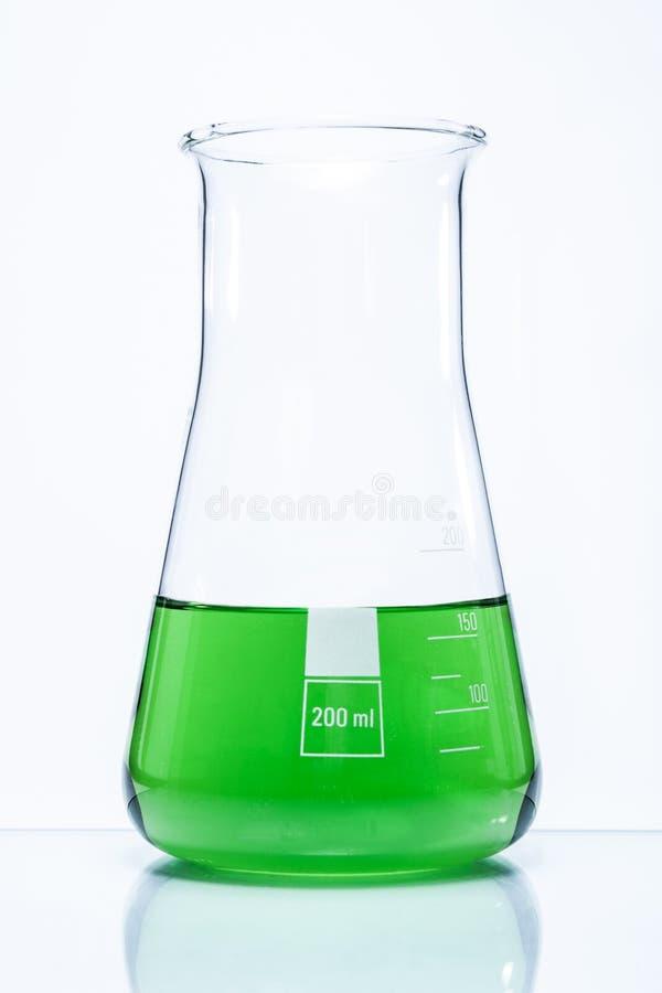 Frasco resistente de la temperatura cónica con el líquido verde fotos de archivo libres de regalías