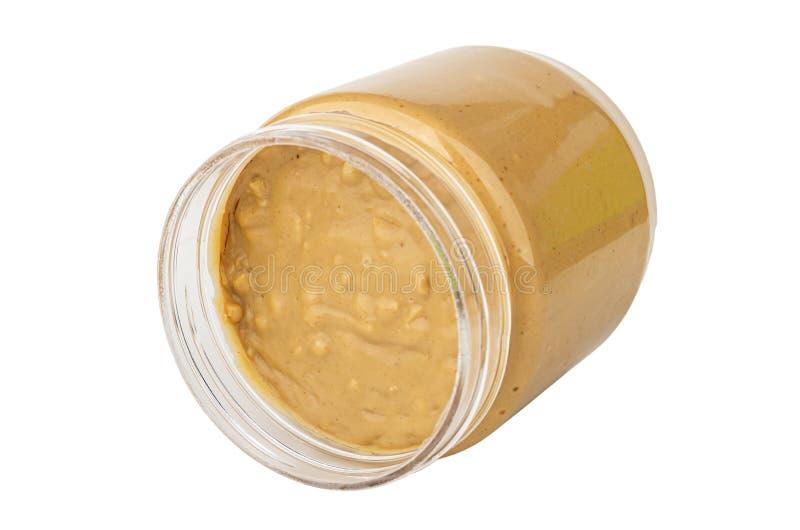Frasco transparente virado com a manteiga de amendoim isolada no branco imagens de stock