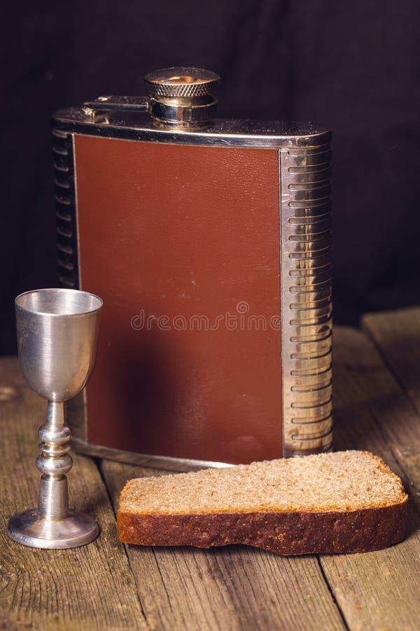 Frasco, vaso de medida y pan en una tabla de madera imagen de archivo