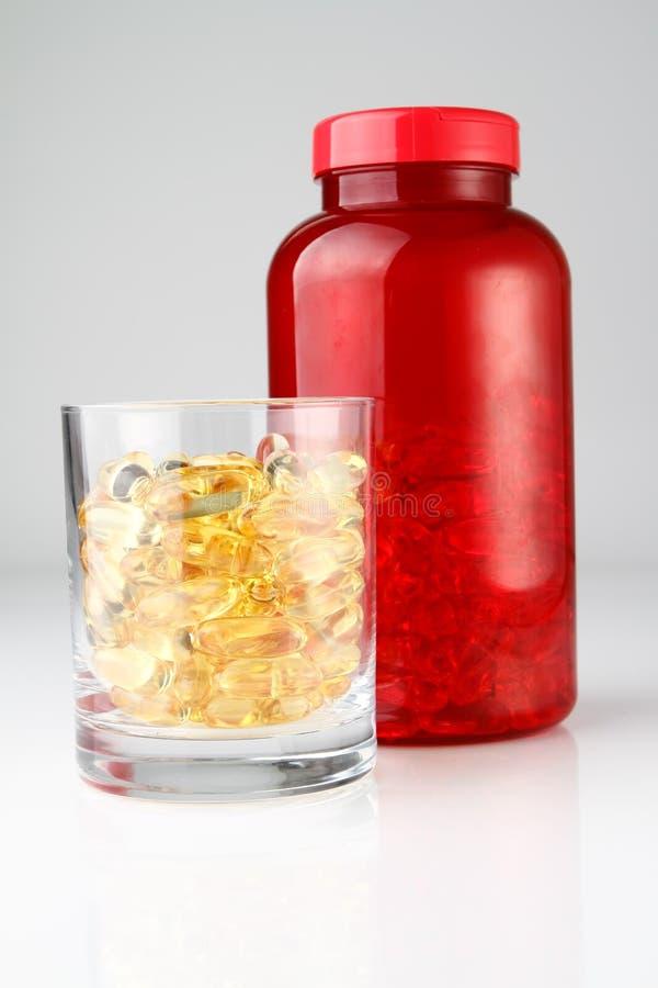 Frasco vermelho com as cápsulas do petróleo no copo de vidro fotos de stock