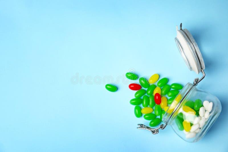 Frasco virado com os feijões de geleia no fundo da cor, vista superior Espa?o para imagem de stock