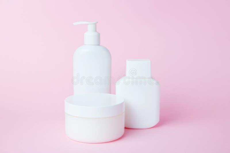Frascos brancos dos cosméticos em um fundo cor-de-rosa Acess?rios do banho Conceito do cuidado da cara e do corpo imagem de stock
