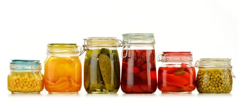 Frascos com vegetais conservados e compotas frutados no branco imagens de stock royalty free
