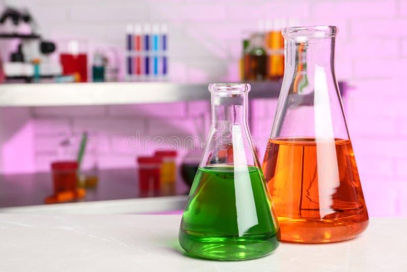 Frascos con las muestras en la tabla en laboratorio de química foto de archivo libre de regalías