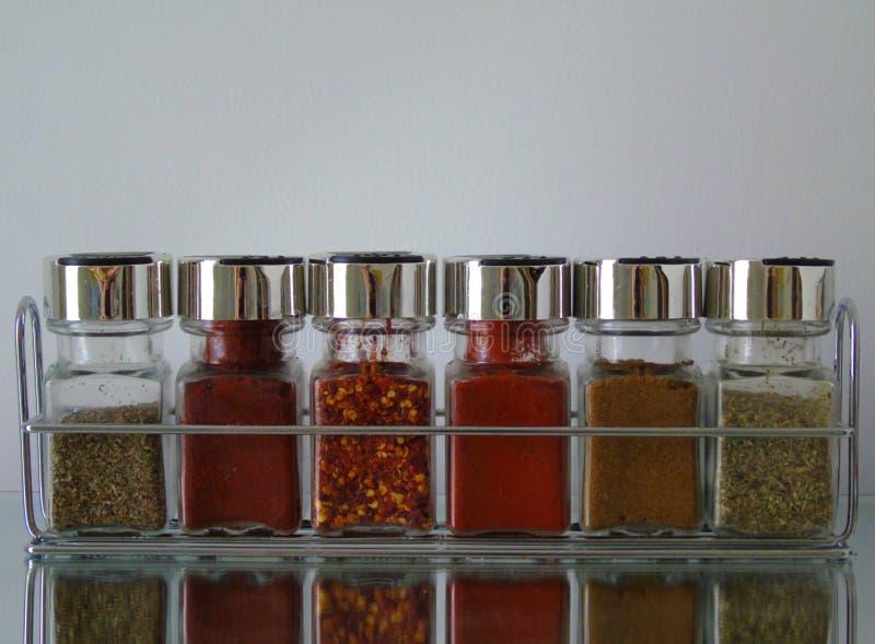 Frascos das ervas e das especiarias na cremalheira de especiaria imagens de stock