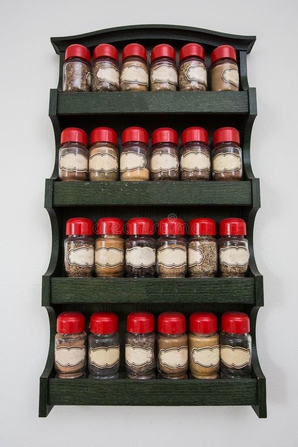 Frascos das ervas e das especiarias na cremalheira de madeira no fundo branco, projeto do vintage fotos de stock