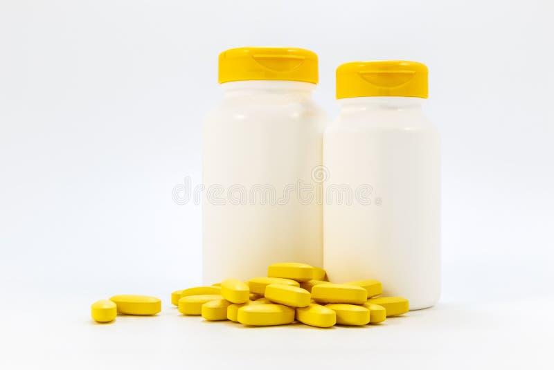 Frascos das medicinas sob os comprimidos que encontram-se em um fundo branco imagem de stock