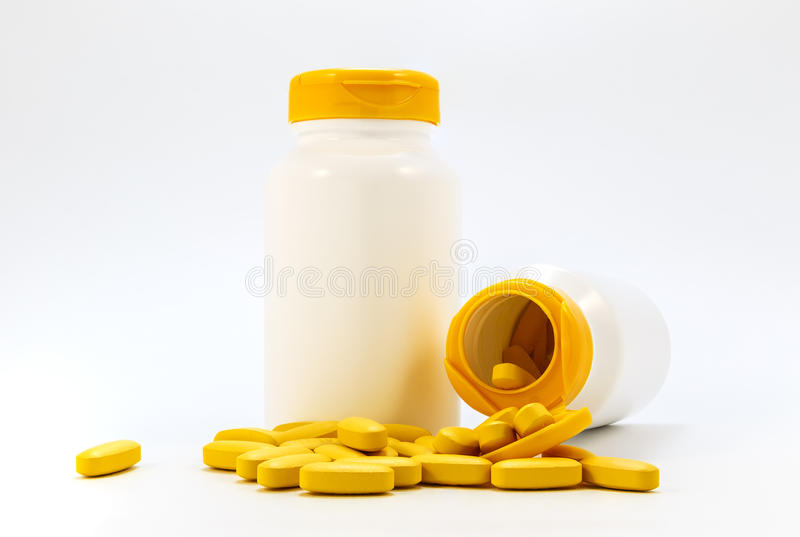 Frascos das medicinas sob os comprimidos que encontram-se em um fundo branco fotos de stock