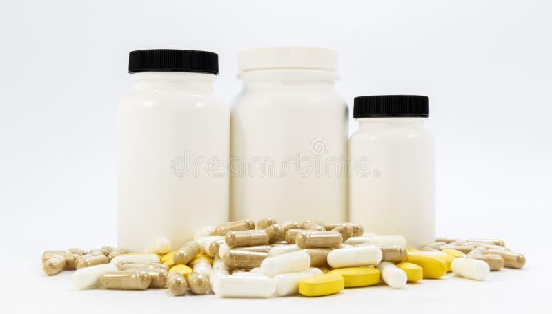 Frascos das medicinas sob os comprimidos que encontram-se em um fundo branco foto de stock royalty free