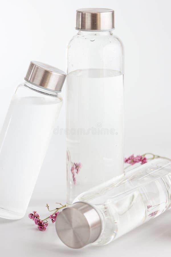 Frascos de água de vidro transparente sobre fundo cinzento brilhante fotografia de stock