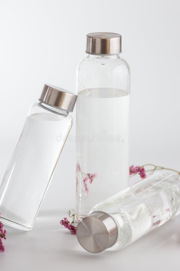 Frascos de água de vidro transparente sobre fundo cinzento brilhante imagem de stock royalty free